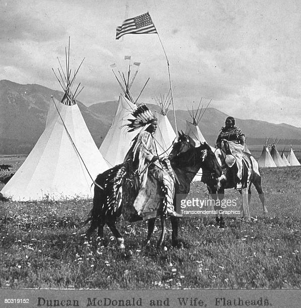 Portrait of Nimi'ipuu tribesman Duncan McDonald and his wife Quilsuh both on horseback before a line of tipi and under a 45star American flag Montana...