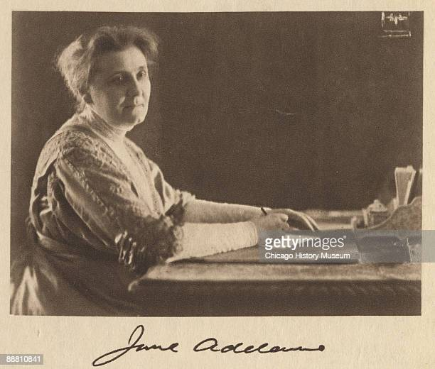 Portrait of Nobel peace prize winner and social activist Jane Addams penning a letter at her desk Chicago IL ca 1890s