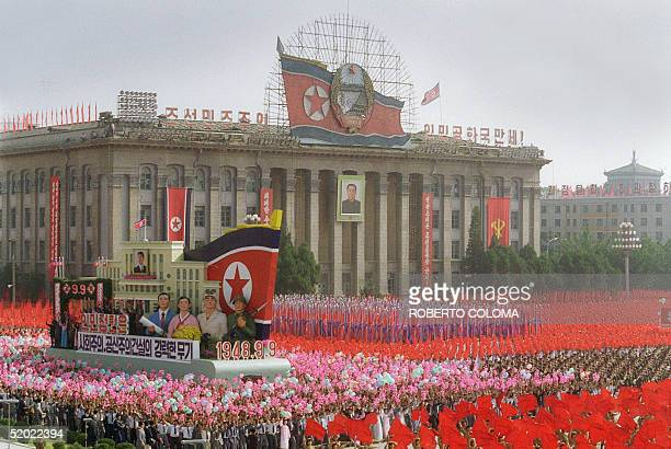 A portrait of North Korean President Kim Ilsung hangs from the facade of an official building in Pyongyang 09 September 1988 while a float to the...