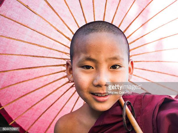 Portrait of novice monk with red umbrella, Myanmar