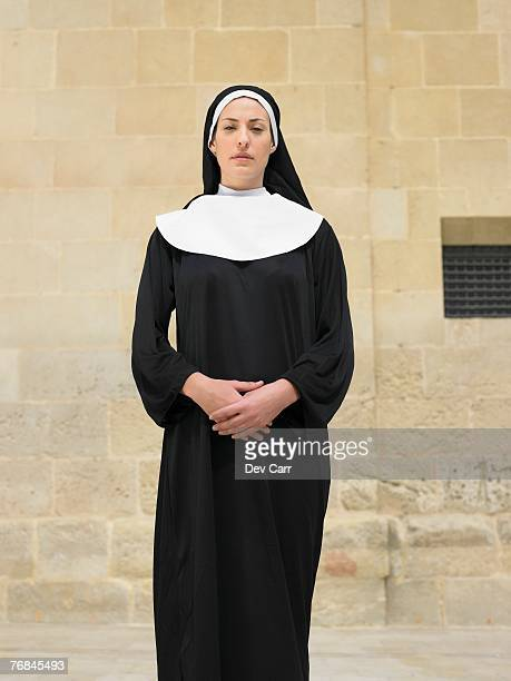 Portrait of nun clasping hands looking into camera, Alicante, Spain,