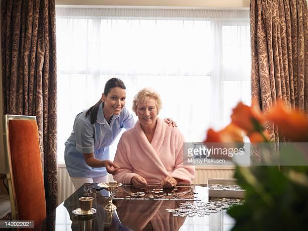 Portrait of nurse assisting senior woman to complete jigsaw puzzle