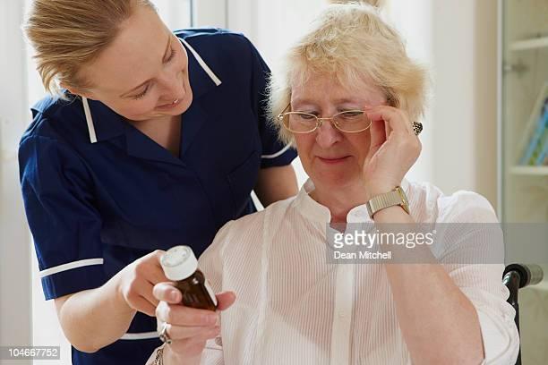 Porträt von Krankenschwester helfen senior Frau mit Medikamente