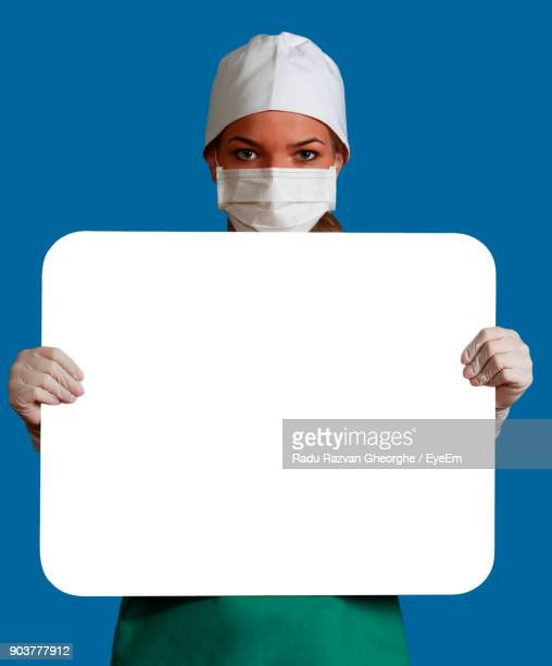 portrait of nurse holding blank placard against blue wall - nursing slogans stock photos and pictures