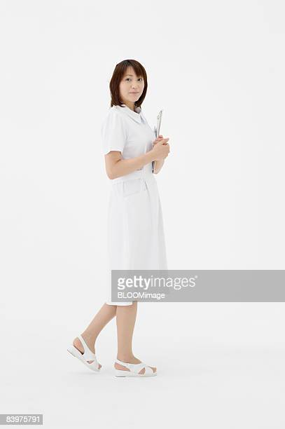 portrait of nurse holding clipboard, studio shot - nurse and portrait and white background and smiling and female and looking at camera stock pictures, royalty-free photos & images