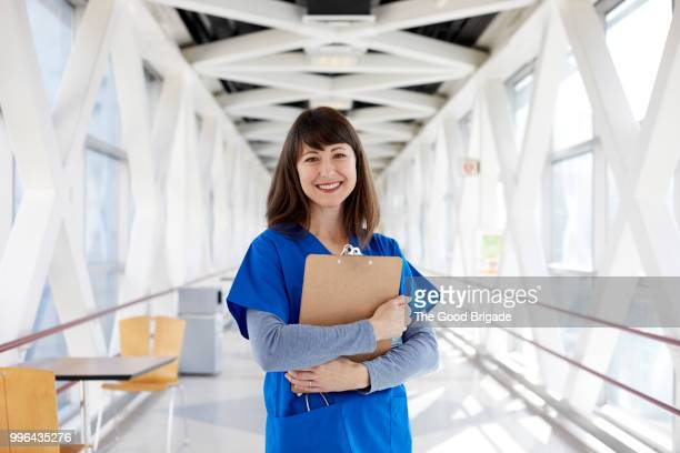 portrait of nurse standing in hospital corridor - hot nurse stock photos and pictures