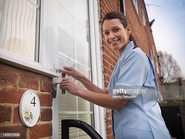 Portrait of nurse unlocking front door of patients house