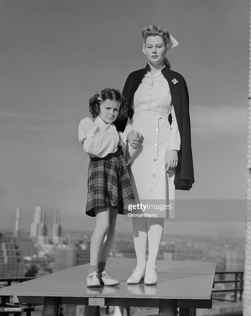 Portrait of nurse with girl on table, cityscape in background : Stock Photo