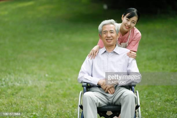 portrait of nurse with senior man in wheelchair - 公共の建物 ストックフォトと画像