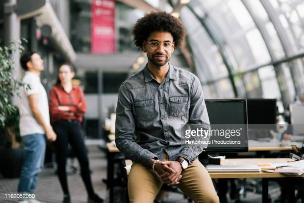 portrait of office employee leaning on desk - black pants stock pictures, royalty-free photos & images