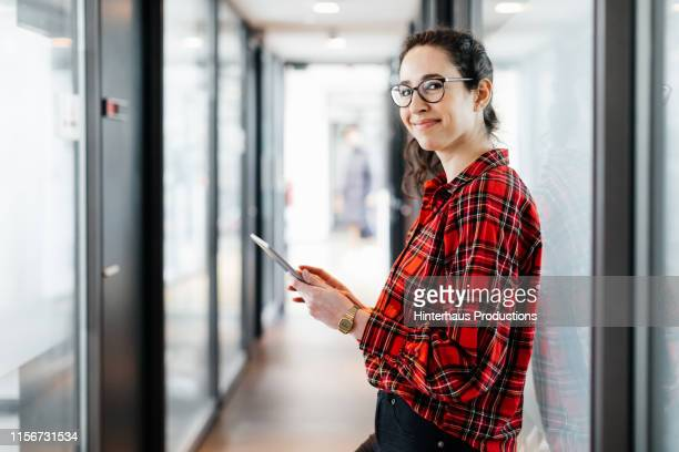 portrait of office employee leaning on window - one mid adult woman only stock pictures, royalty-free photos & images