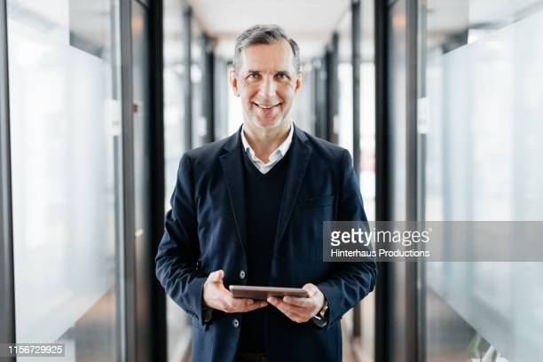portrait of office manager holding digital tablet - anzug stock-fotos und bilder