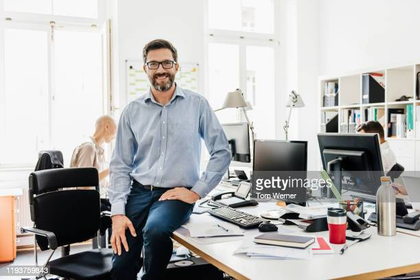 portrait of office manager perched on computer desk - 40 44 years stock pictures, royalty-free photos & images