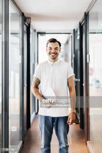 portrait of office worker in hallway - polo shirt stock pictures, royalty-free photos & images