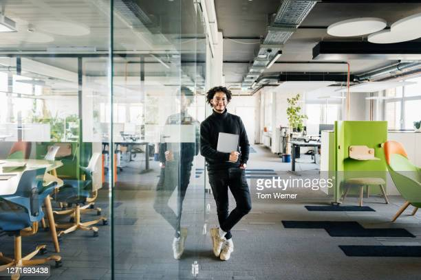 portrait of office worker leaning on glass pane - black colour stock pictures, royalty-free photos & images