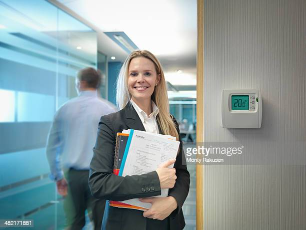 Portrait of office worker next to office thermostat adjusted to make energy savings