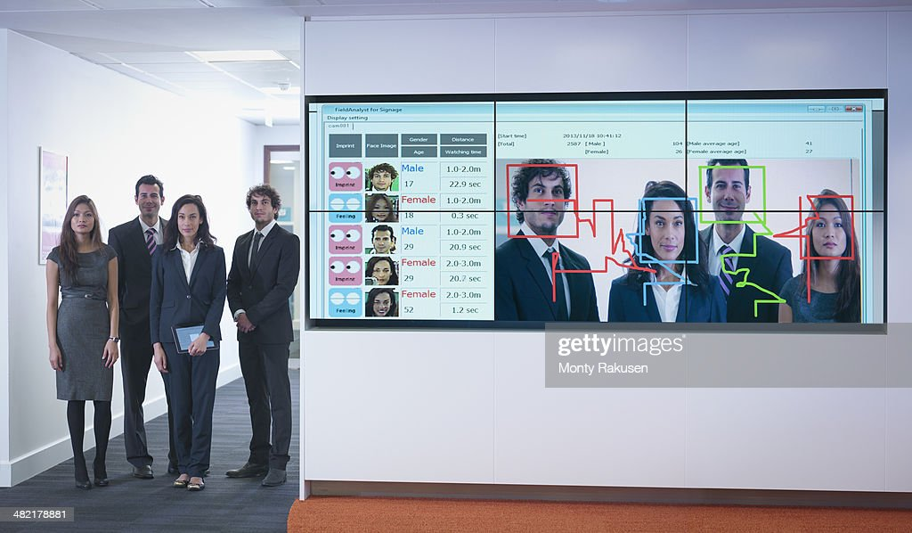 Portrait of office workers standing next to face recognition software system : Stock Photo