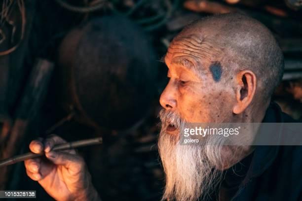 Porträt des alten chinesischen Mann-Pfeife