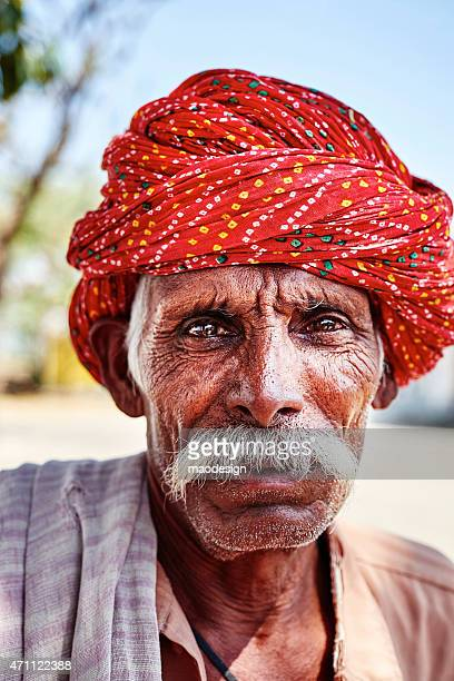 Portrait of old indian man with red headscarf showing power