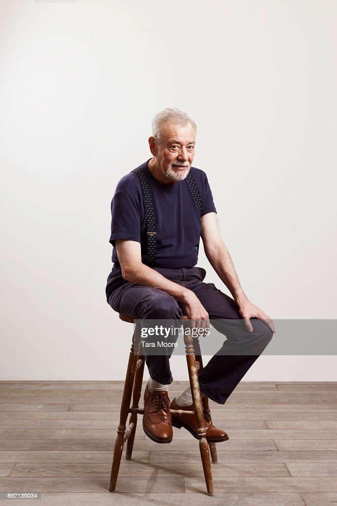Portrait of old man sitting on chair : Stock Photo