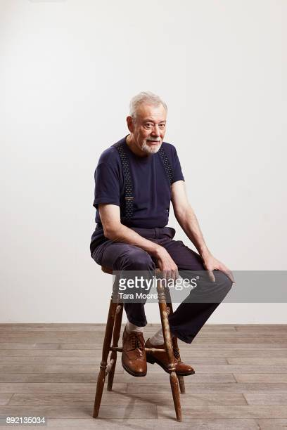 portrait of old man sitting on chair - sitzen stock-fotos und bilder