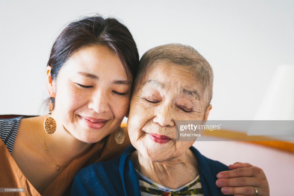 Portrait of old mother with cancer and her middle aged daughter : Stock Photo