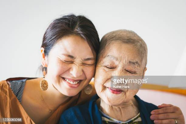 portrait of old mother with cancer and her middle aged daughter - love stock pictures, royalty-free photos & images