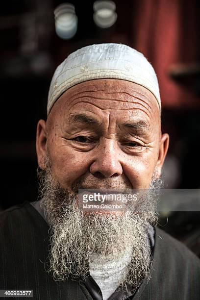 CONTENT] Portrait of old muslim man of uyghur ethnicity wearing traditional hat at the livestock market of Kashgar Xinjiang China