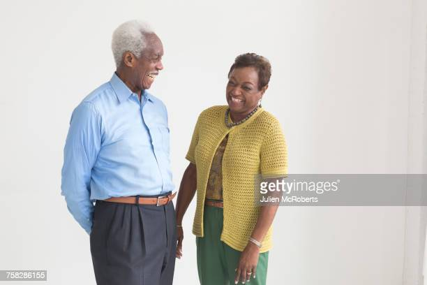 portrait of older black couple laughing - driekwartlengte stockfoto's en -beelden