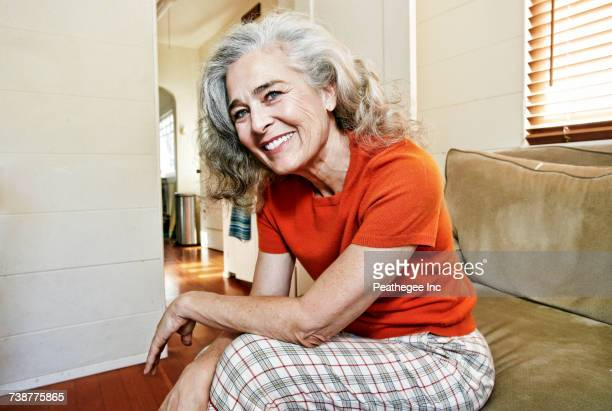 Portrait of older Caucasian woman sitting on sofa