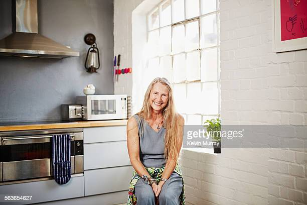 A portrait of older woman sitting in a kitchen
