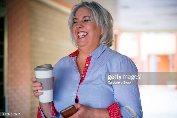 portrait of one mature woman laughing with a reusable coffe cup - 50 59 years stock pictures, royalty-free photos & images