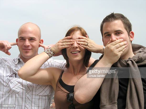 CONTENT] Portrait of one woman and two men who simulate the three wise monkeys by covering the eyes the ears and the mouth The young guys want to...