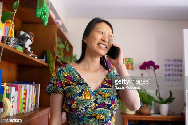 portrait of one woman at home on mobile phone - showus stock pictures, royalty-free photos & images