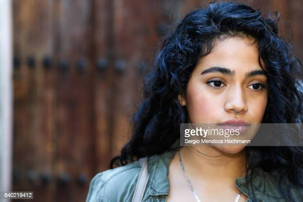 Portrait of one young Hispanic woman looking away from camera in Mexico City