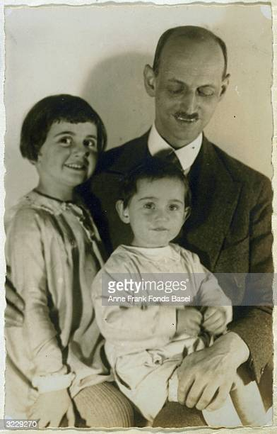 Portrait of Otto Frank holding his daughters Margot and Anne on his lap taken from the photo album of Anne Frank Frankfurt am Main Germany
