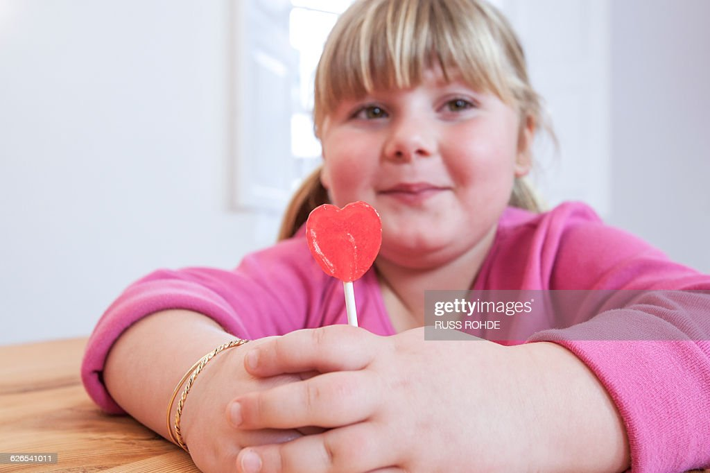 Portrait of overweight girl holding heart shape lollipop : Stock Photo