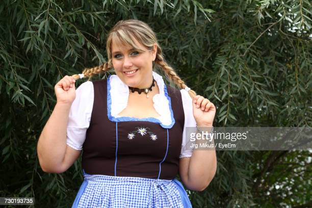 Portrait Of Overweight Smiling Woman Holding Pigtails While Standing Against Plants