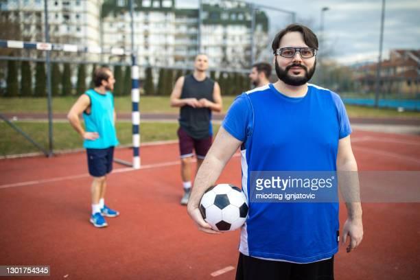 ritratto di calciatore in sovrappeso su campo da calcio all'aperto - fat soccer players foto e immagini stock