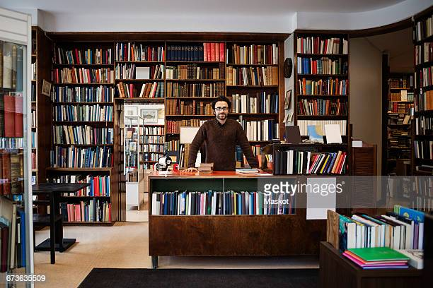 portrait of owner standing against bookshelves in library - bookstore stock pictures, royalty-free photos & images