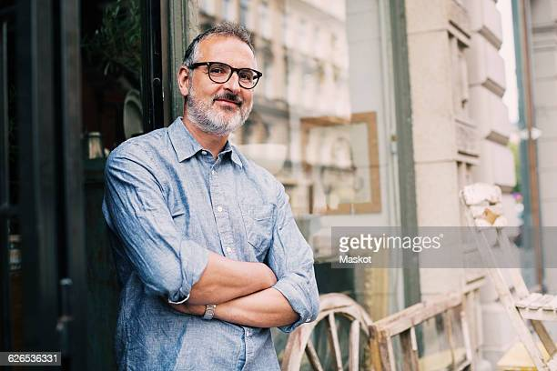 Portrait of owner standing with arms crossed outside antique shop