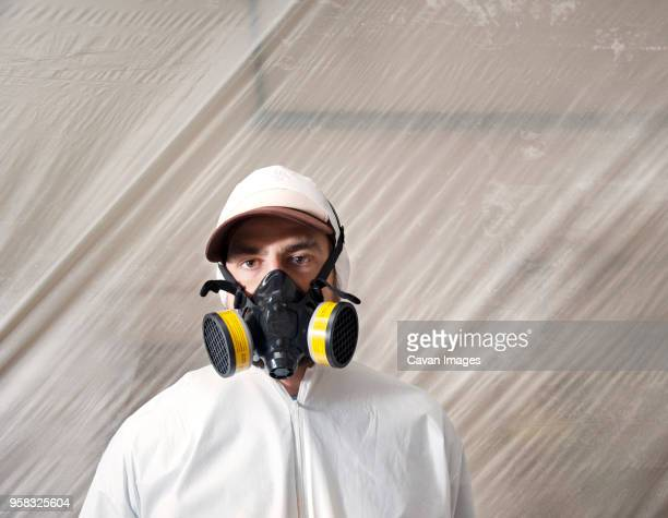 portrait of painter with gas mask against plastic in workshop - gas mask stock pictures, royalty-free photos & images