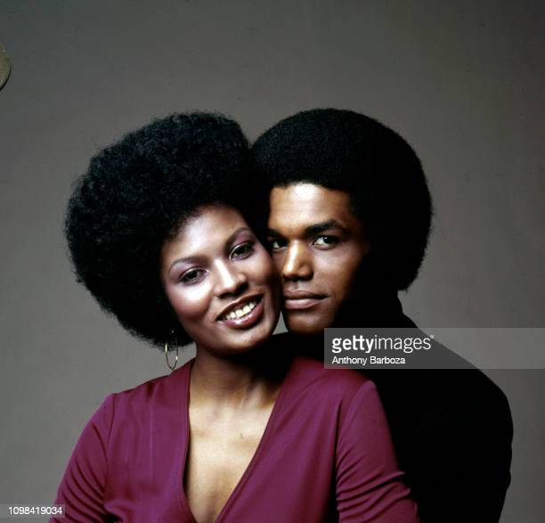 Portrait of pair of unidentified models both with Afro hairstyles as they pose indoors against a gray background New York 1970