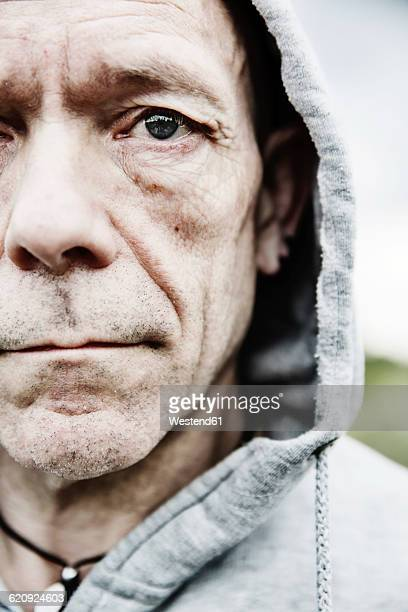 Portrait of pale man wearing hooded jacket, close-up
