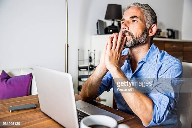 Portrait of pansive businessman working with laptop at home office