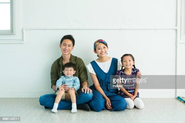 Portrait of parents and children, sitting on floor