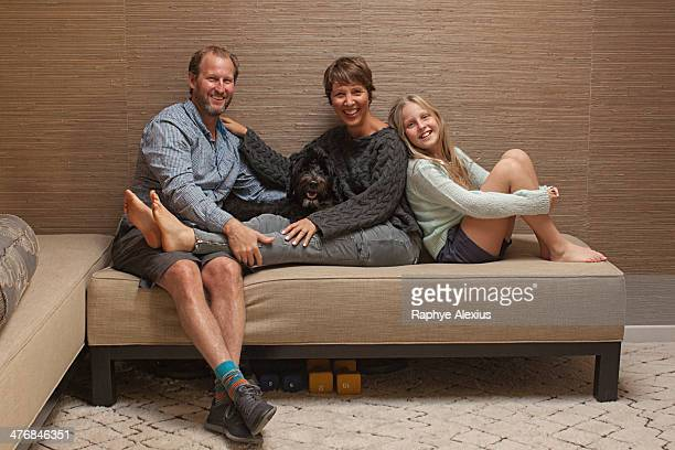 Portrait of parents and daughter on sofa