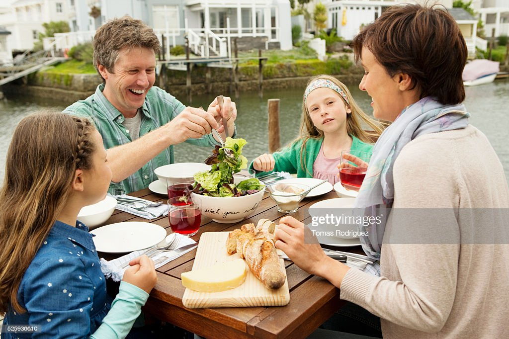 Portrait of parents and girls (6-7), (8-9) eating outdoors : Stockfoto