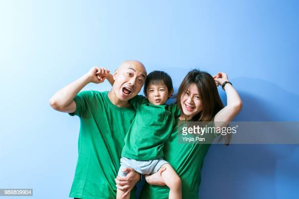 portrait of parents and son in front of blue background - family with one child stock pictures, royalty-free photos & images