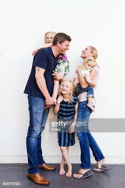 Portrait of parents and three young daughters in front of white wall